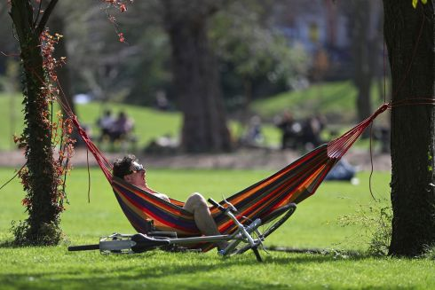 HANGING OUT: Ryan Aylward sunbathes from his hammock at Merrion Square, Dublin. Photograph: Nick Bradshaw