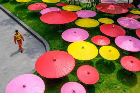 PAPER UMBRELLAS: A security guard walks past a decorative installation made of colourful paper umbrellas outside a shopping mall in Bangkok, Thailand. Photograph: Mladen Antonov/AFP via Getty