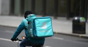 A Deliveroo rider cycling through central London. Within minutes of the market opening on Wednesday, Deliveroo  lost £2.28bn  of its value. Photograph: Daniel Leal-Olivas/AFP via Getty Images