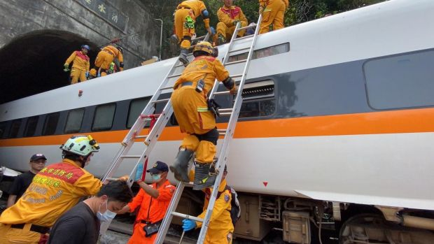 Rescuers working on a train which derailed in a tunnel north of Hualien County, eastern Taiwan. Photograph: Keelung City Fire Department/EPA