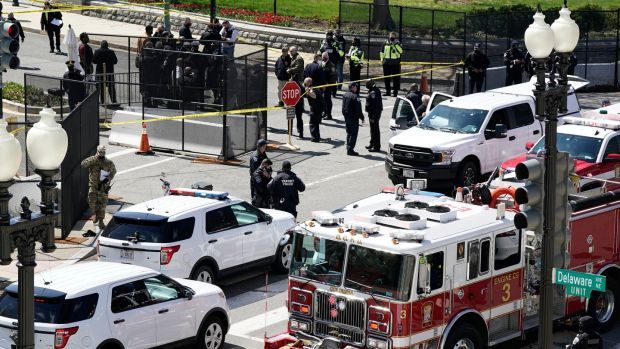 Police and fire officials stand near a car that rammed into a barrier on Capitol Hill in Washington on Friday. Photograph: J Scott Applewhite/AP