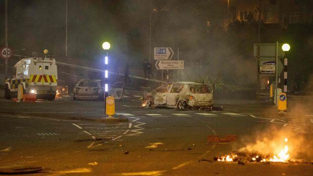 A damaged car and flames in Newtownabbey, Belfast, Northern Ireland. Photograph: Paul Faith/AFP via Getty