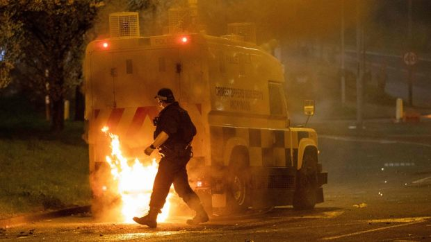 A police officer walks behind a police vehicle as flames engulf the rear following violence in Newtownabbey, Belfast, Northern Ireland. Photograph: Paul Faith/AFP via Getty