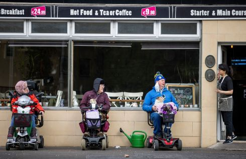 ORDERLY QUEUE: Mairin De Burca (left), Tim Rodgers (with his Chihuahua Rocky) and Tom McKiernan (with his Jack Russell called Snowy) queuing outside the  Green Land Cafe, Fairview, with server Yo Yo Liu taking their order. Photograph: Tom Honan