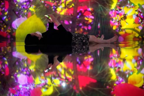 BOWLED OVER: A journalist lies down to fully take in a digital artwork entitled Floating in the Falling Universe of Flowers by Japanese creative group teamLab, presented during a press preview in Tokyo, Japan. Photograph: Franck Robichon/EPA