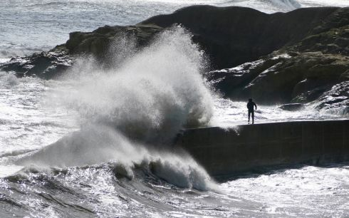 PLEASE BE NIMBLE: A man tries to dodge heavy waves crashing over the sea wall at Cullercoats, near Tynemouth, Northumberland, England. Photograph: Owen Humphreys/PA Wire