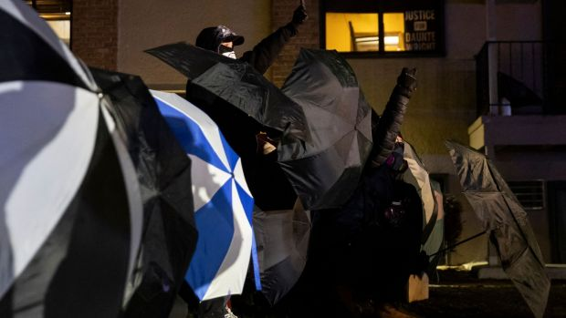 Protesters protect themselves with umbrellas against tear gas and pepper balls outside the Brooklyn Center police station during a semonstration on Tuesday. Photograph: Getty Images