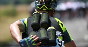 A cyclist of Russia's Tinkoff cycling team carrying feeding gfbottles for his teammates rides during the Tour de Frnace. Photograph: Kenzo Tribouillard/AFP/Getty Images. /
