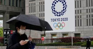People walk past a banner with the logo of the Tokyo 2020 Olympic Games hanging from the wall of the Tokyo Metropolitan City Hall. Photograph: Kimimasa Mayama/EPA