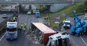 TRAFFIC INCIDENT: M50 staff work to get a lorry, which overturned on the motorway's northbound carriageway under the Red Cow intersection, back on its wheels on Thursday morning. The lorry caused huge tailbacks on the M50 for a period of time. Photograph: Colin Keegan/Collins Dublin