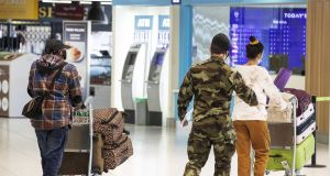 A member of the defence forces escorts passengers from Terminal 1 arrivals hall at Dublin Airport as part of the State's mandatory quarantine system. Photoggraph:  Brian Lawless/PA Wire