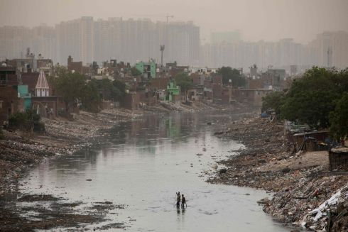 BEFORE THE STORM: People wade across a sewage canal before a sandstorm in Noida on April 16th. Photograph: Xavier Galiana/AFP via Getty