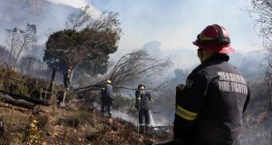 Firefighting teams dampen smouldering vegetation on the foothills of Table Mountain in Cape Town on Monday. Photograph: Rodger Bosch/AFP via Getty Images