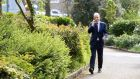 AFFAIRS OF STATE: Taoiseach Micheál Martin on the phone while taking some fresh air in Merrion Square, Dublin. Photograph: Dara Mac Dónaill