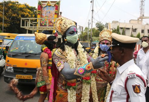 RAMA DRAMA: Men dressed in the image of Hindu god Lord Rama wear protective face masks as they give a mask to a traffic policeman during a Covid-19 awareness campaign in Bangalore, India. The country has recorded a massive surge of 294,291 fresh daily cases, the highest single-day spike in Covid-19 infections. Photograph: Jagadeesh NV/EPA