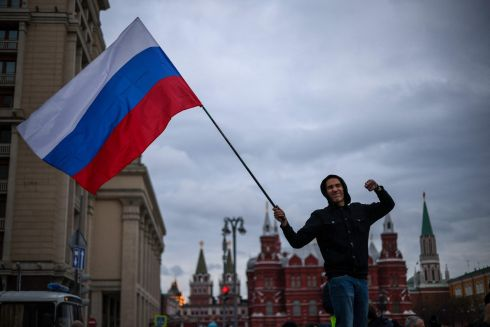 SUPPORTING NAVALNY: An opposition supporter waves a Russian national flag during a rally in Moscow in support of jailed Kremlin critic Alexei Navalny. Mr Navalny's team called for demonstrations in more than 100 cities after the opposition figure's doctors said his health was failing after three weeks on hunger strike. Photograph: Dimitar Dilkoff/AFP/Getty
