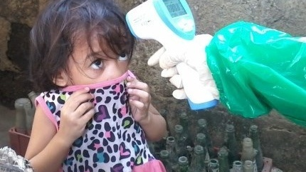 Three-year-old Desiree Pajo has her temperature taken in Sitio Marna