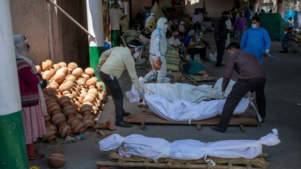 People line up bodies of those who died of Covid-19 at a crematorium in New Delhi. Photograph: Altaf Qadri/AP