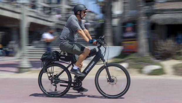 A man rides an electric bicycle nin Huntington Beach, California, in April. Photograph: Paul Bersebach/Orange County Register via Getty Images