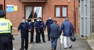 Gardaí at the scene of                   this week's murder at Robinson's Court as local                   residents pass by. Photograph: Nick Bradshaw