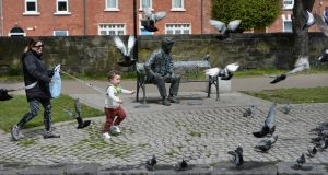 CATCH THE BIRDIE: Michelle Lindsay restrains her son Koben as he tries to pursue pigeons beside the Brendan Behan bench along the Royal Canal, in Drumcondra, Dublin. Photograph: Dara Mac Dónaill