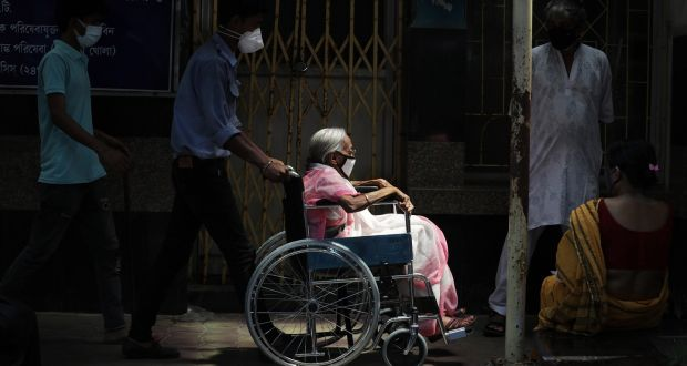 Relatives push an elderly woman in a wheelchair as she arrives for a Covid-19 vaccination at a government hospital in Kolkata, India. Photograph: Piyal Adhikary/EPA