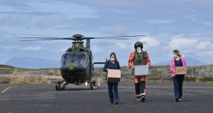 VACCINE DELIVERY: Nurses Margaret Lavelle (left) and Louise Fleming take delivery of Covid-19 vaccines from an Irish Air Corps crew member on Inishbofin. The Government has tasked the Air Corps to transport vaccines to some of Ireland's most remote islands. Photograph: Charles McQuillan/Getty