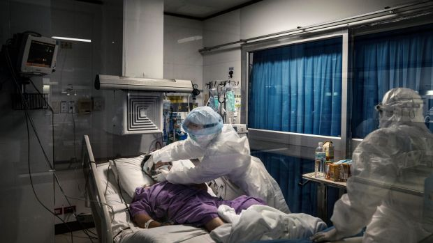 A nurse secures the mask of a Covid-19 patient in the intensive care section of a private hospital in Bangkok. Photograph: Adam Dean/The New York Times