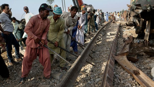 Railway workers rebuild the track at the site of the collision in Ghotki. Photograph: Fareed Khan/AP