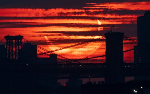 SOLAR ECLIPSE: A partial solar eclipse rises beyond bridges crossing the East River in New York, US. Thursday's event was at its most pronounced on a path beginning in Canada and travelling across Greenland, close to the North Pole and down into eastern Europe. Photograph: Justin Lane/EPA