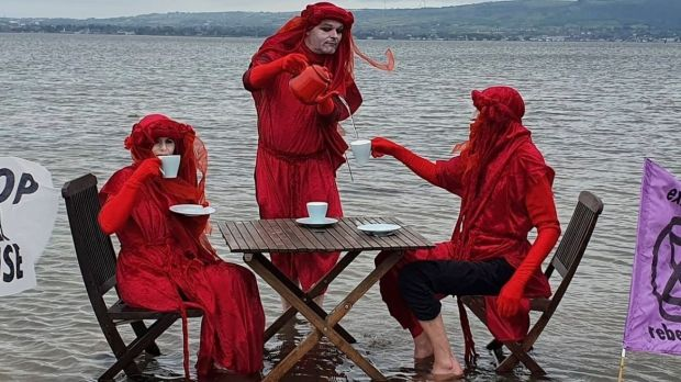 Off the Down coast Extinction Rebellion Northern Ireland members dress as red rebels and serve tea at a table half submerged in the sea to highlight rising sea levels