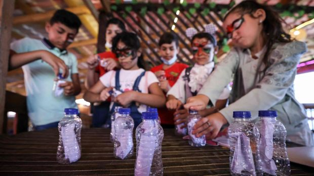 Palestinian students in Gaza  who received letters from US children, prepare messages in bottles as a response. Photograph:  Mahmud Hams/AFP via Getty