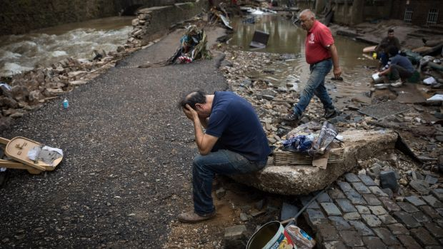 A restaurateur holds his head in his hands outside his business in Bad Münstereifelafter catastrophic flooding in west Germany. Photograph: New York Times