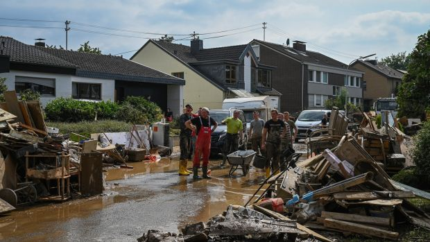 Volunteers clean the streets around the Haus Lebenshilfe care home, where 12 sleeping residents died in the flooding, in Sinzig, Germany, on Saturday. Photograph: The New York Times