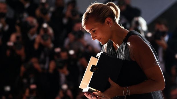 """TOPSHOT - La réalisatrice française Julia Ducournau pose avec son trophée lors d'un photocall après avoir remporté la Palme d'Or pour le film """"Titane"""" lors de la cérémonie de clôture de la 74e édition du Festival de Cannes à Cannes, dans le sud de la France, le 17 juillet 2021. (Photo de CHRISTOPHE SIMON / AFP) (Photo de CHRISTOPHE SIMON/AFP via Getty Images)"""