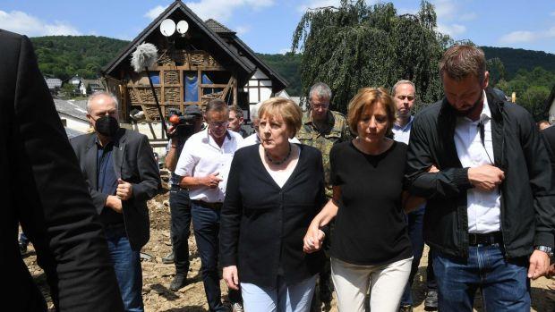 German chancellor Angela Merkel and Rhineland-Palatinate state premier Malu Dreyer walk through the flood-ravaged village of Schuld. Photograph: Christof Stache/Pool/AFP via Getty