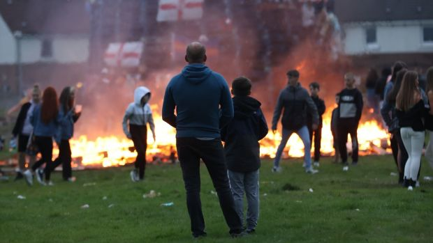 People stand by as the Galliagh bonfire is lit in Derry. Photograph: Liam McBurney/PA Wire