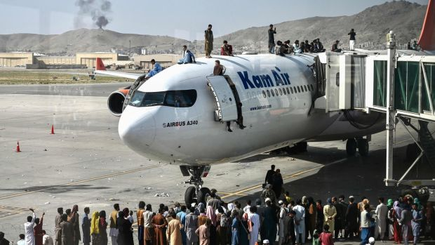 Afghan people climb on top of an aircraft as they wait at the Kabul airport on Monday. Photograph: Wakil Kohsar/AFP via Getty Images