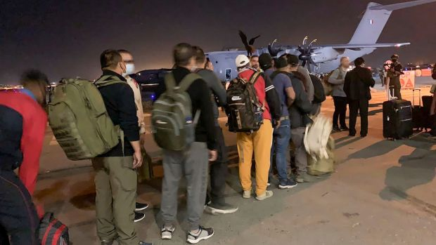 French nationals and their Afghan colleagues line up to board a French military transport plane at Kabul airport. Photograph: AFP via Getty Images