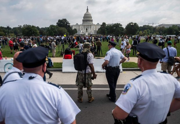 Police officers watch demonstrators taking part in the 'Justice for J6' rally in Washington DC on Saturday. Photograph: Andrew Caballero-Reynolds/AFP via Getty